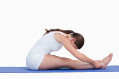 Young woman sitting on a yoga mat Royalty Free Stock Images