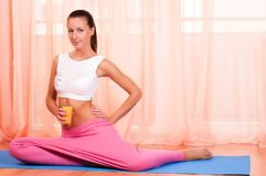 Young woman sitting on a yoga mat Stock Photography