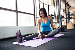 Young woman sitting on yoga mat and using smartphone Royalty Free Stock Image