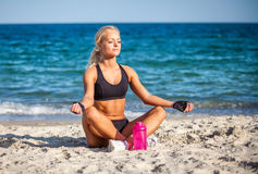 Young woman sitting in yoga pose at the beach Royalty Free Stock Images