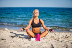 Young woman sitting in yoga pose at the beach Stock Photo