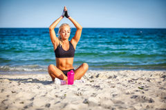 Young woman sitting in yoga pose at the beach Stock Image