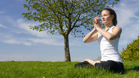 Young woman sitting in a yoga pose in beautiful nature surroundings Royalty Free Stock Photography