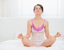 Young woman sitting in yoga pose on bed Stock Image