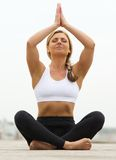 Young woman sitting in yoga pose outdoors Stock Photo