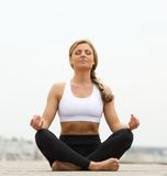 Young woman sitting in yoga pose outside Royalty Free Stock Images