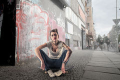 Young woman on a skateboard. Young beautiful women with tattoos sitting on a skateboard stock photography