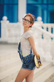 Young woman with a skateboard on the street of the city Royalty Free Stock Photo