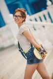 Young woman with a skateboard on the street of the city Royalty Free Stock Photography