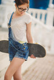 Young woman with a skateboard on the street of the city Royalty Free Stock Photos