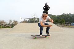 Young woman skateboarder skateboarding at skatepark Stock Photography