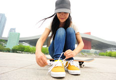 Young woman skateboarder tying shoelace Stock Photo