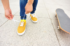 Young woman skateboarder tying shoelace Royalty Free Stock Photo