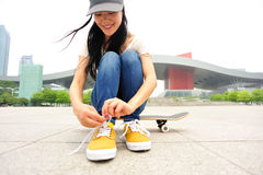Young woman skateboarder tying shoelace Royalty Free Stock Images