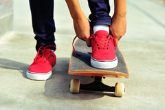 Young woman skateboarder tying shoelace Royalty Free Stock Photos