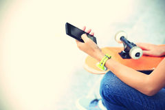 Young woman skateboarder use smart phone in city Royalty Free Stock Photography