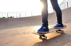 Young woman skateboarding legs at sunrise Royalty Free Stock Photo
