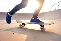 Young woman skateboarding legs at sunrise Royalty Free Stock Images