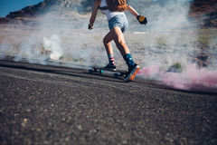 Young woman skateboarding on a road Stock Photo
