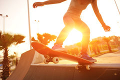 Young woman skateboarding at sunrise Royalty Free Stock Images