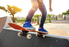 Young woman skateboarding at sunrise Stock Photo