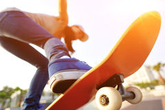 Young woman skateboarding at sunrise Stock Photos