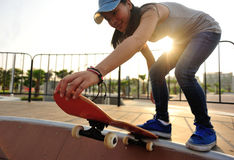 Young woman skateboarding at sunrise Stock Images