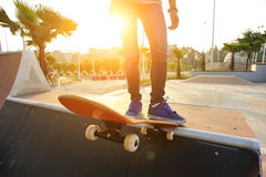 Young woman skateboarding at sunrise Stock Photography