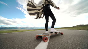 Young woman with skating board on blue sky background stock video