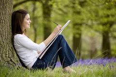 A young woman with sketchbook sitting against a tree trunk in a field of bluebells Stock Photography