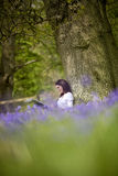 A young woman with sketchbook sitting against a tree trunk in a field of bluebells Royalty Free Stock Photos