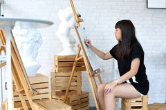 Young woman sketching on easel stock photos