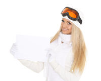 Young  woman in ski glasses with empty board for the text. Royalty Free Stock Images