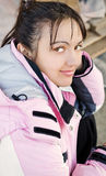 Young woman in ski jacket outdoor. Young woman looks with interest in eyes, smiles Royalty Free Stock Images