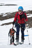 Young woman ski mountaineer climb on mountain on skis strapped to climbing skins Royalty Free Stock Photography