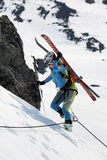 Young woman ski mountaineer climbing on rope on rock Royalty Free Stock Images