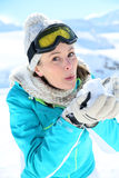 Young woman in ski outfit blowing snowflakes Stock Photography