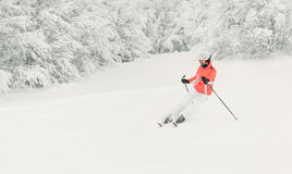 Young woman skier skiing fast downhill on ski slope  Royalty Free Stock Image