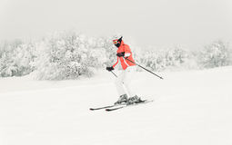 Young woman skier skiing fast downhill on ski slope Stock Photo