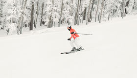Young woman skier skiing fast downhill on ski slope Stock Photos