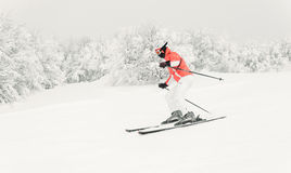 Young woman skier skiing downhill on ski slope Royalty Free Stock Photo