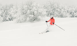 Young woman skier running downhill on ski piste Royalty Free Stock Image