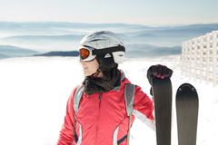 Young woman skier at winter ski resort in mountains, holding skies Royalty Free Stock Image