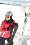 Young woman skier at winter ski resort in mountains, holding skies Stock Photo