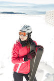Young woman skier at winter ski resort in mountains, holding skies Stock Image