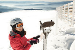 Young woman skier at winter ski resort in mountains reading map, finding path Royalty Free Stock Image