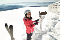 Young woman skier at winter ski resort in mountains reading map, finding path Royalty Free Stock Images