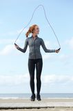 Young woman skipping with jump rope outdoors Stock Photo