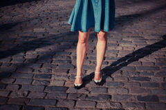Young woman in skirt walking on a cobbled street Stock Photography