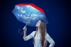 Young woman with sky design umbrella on dark blue background. Clothing and accessories. Graphic design. Fashion goods royalty free stock image